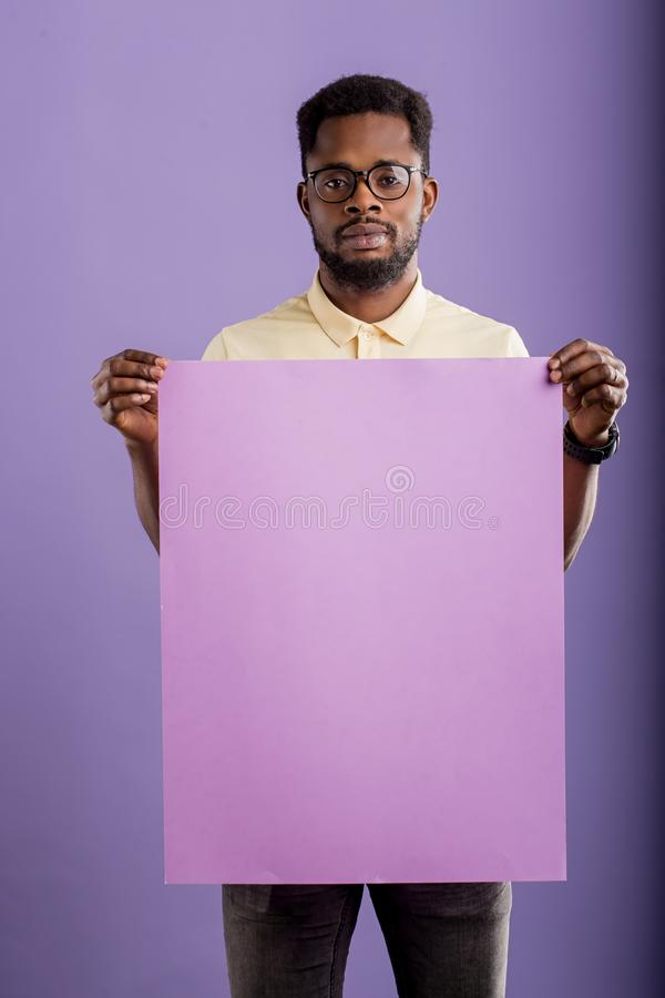 Picture of young african american man holding blank board on violet background stock images