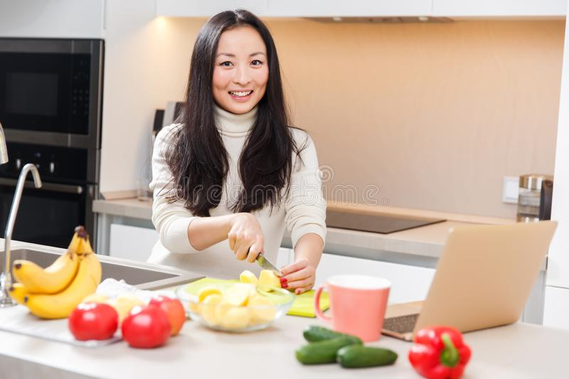 Picture of young asian girl with mug and laptop standing at table with vegetables and fruits stock images