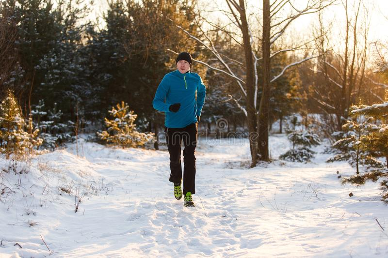 Picture of young athlete running through winter forest royalty free stock photos