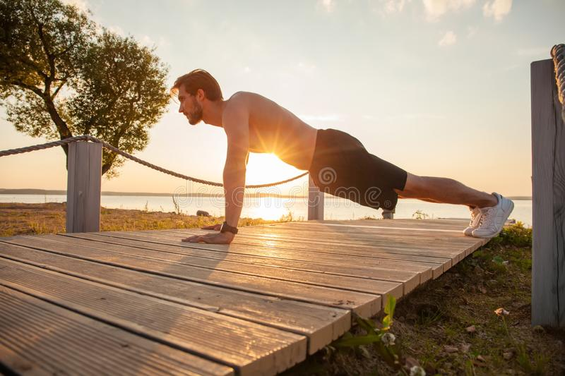 Picture of a young athletic man doing push ups outdoors.  royalty free stock photos