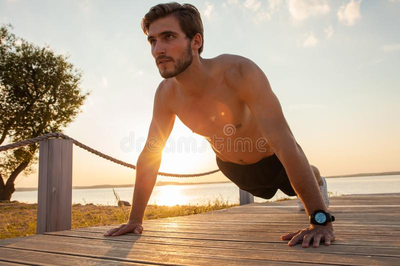 Picture of a young athletic man doing push ups outdoors.  royalty free stock photography