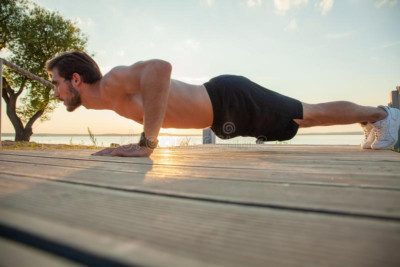 Picture of a young athletic man doing push ups outdoors.  stock image