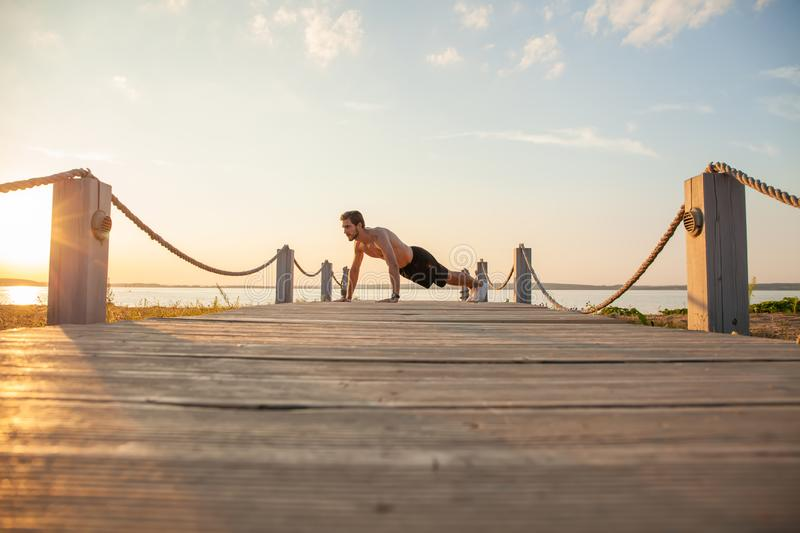 Picture of a young athletic man doing push ups outdoors.  royalty free stock photo