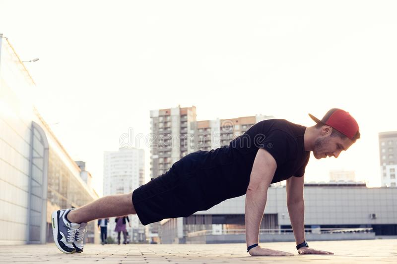 Picture of a young athletic man doing push ups outdoors.Fitness and exercising outdoors urban environment. royalty free stock images