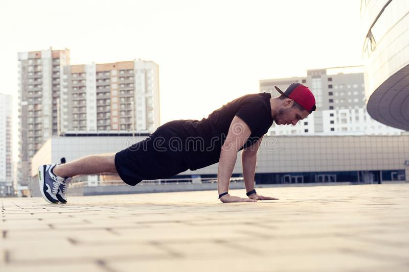 Picture of a young athletic man doing push ups outdoors.Fitness and exercising outdoors urban environment. Picture of a young athletic man doing push ups stock photography