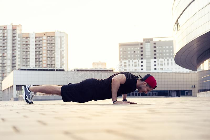 Picture of a young athletic man doing push ups outdoors.Fitness and exercising outdoors urban environment. Picture of a young athletic man doing push ups royalty free stock images