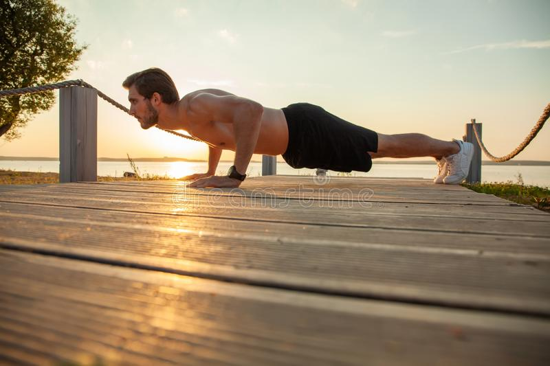 Picture of a young athletic man doing push ups outdoors.  stock images