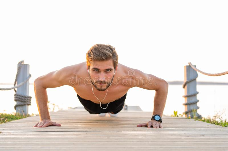 Picture of a young athletic man doing push ups outdoors.  royalty free stock image