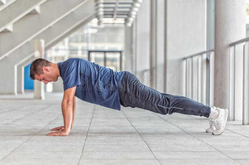 Young sporty man doing push ups. Picture of a young athletic man doing push ups in a sports center, preparing for morning workout stock photography
