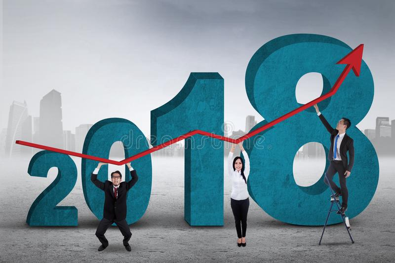 Business people making an upward arrow. Picture of young business people making an upward arrow while standing with numbers 2018 stock photography