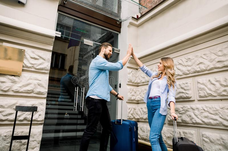 Picture of young couple smiling and giving five while entering hotel. Happy couple with suitcases standing near the old stock photos