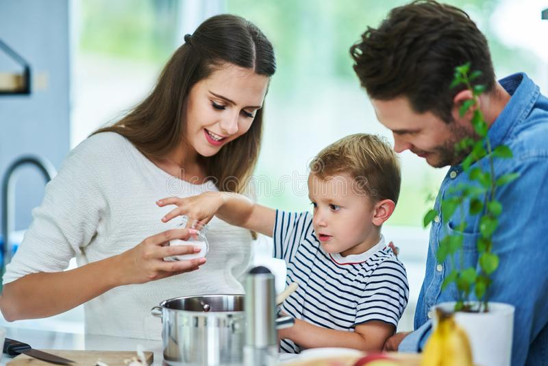 Young family spending time together in the kitchen. Picture of young family spending time together in the kitchen royalty free stock photos
