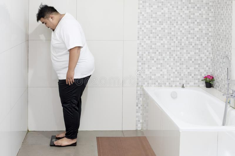 Young fat man checking his weight by scale. Picture of young fat man checking his weight while standing on the scale. Shot in the bathroom royalty free stock image