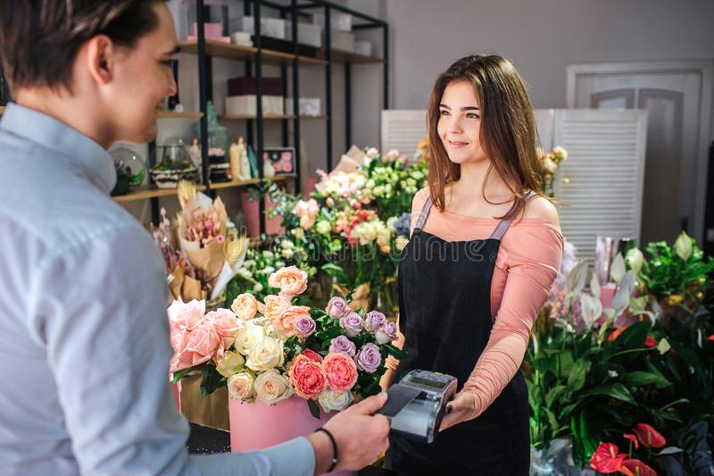 Picture of young female florist holding money therminal. She stand in front of customer. Young businessman pay for royalty free stock photography