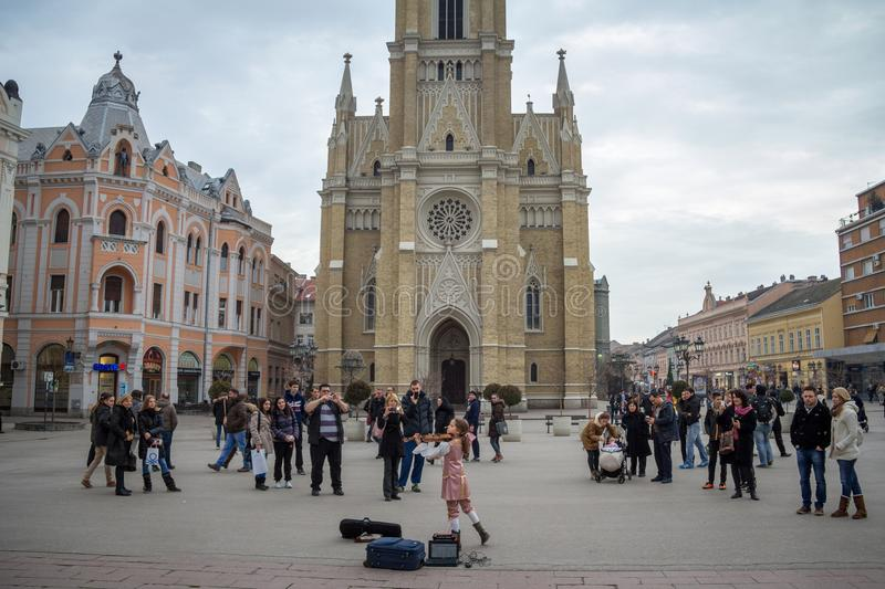 Crowd gathered on Trg Slobode square to listen to a young girl playing violin in front of The Name of Mary Church, stock images