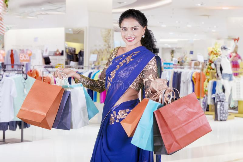 Indian woman carries shopping bags in the mall royalty free stock photography