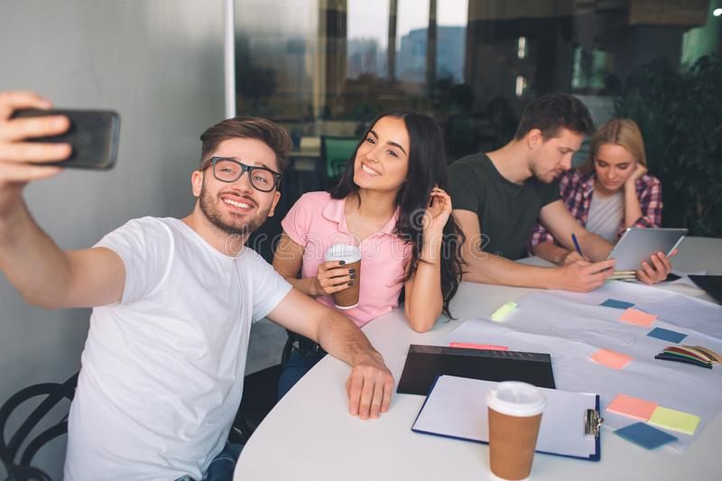 Picture of young man holding phone and take selfie with beautiful brunette. They pose and smile. Another couple sit royalty free stock photography