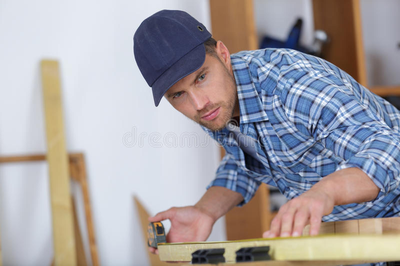 Picture young man working as carpenter and measuring board royalty free stock photos