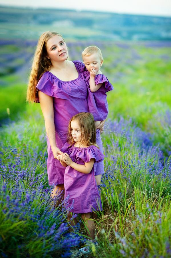 Cheerful young woman with two young girls on the background of beautiful nature in spring royalty free stock photos
