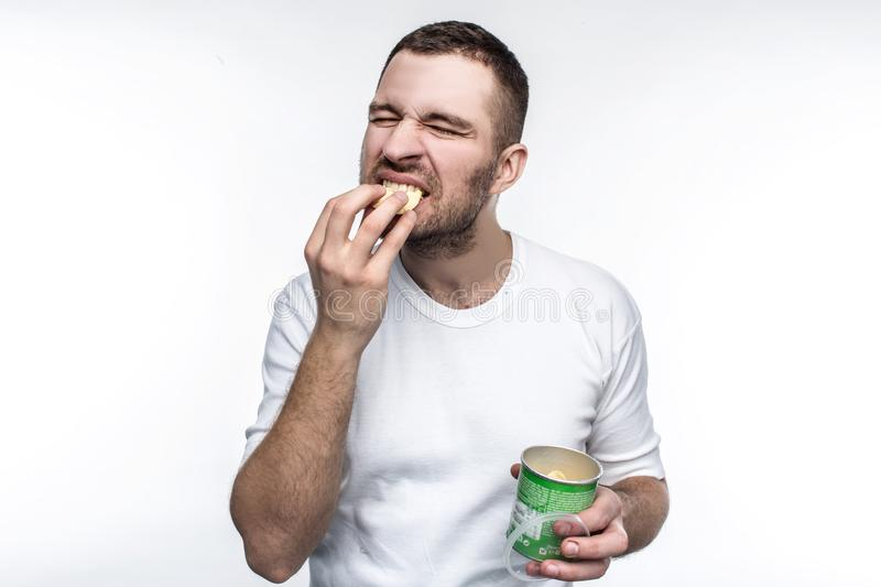 A picture of young nd weird man eating chips from the jar. This food is not healthy and good but he likes it. He is full royalty free stock images