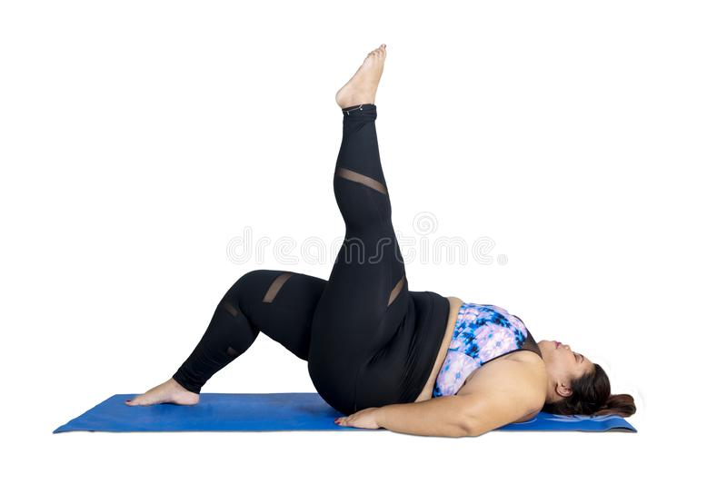 Obese woman lifting her leg during yoga exercises. Picture of young obese woman lifting her leg while doing yoga exercise in the studio, isolated on white stock photo