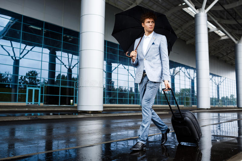 Picture of young redhaired businessman holding black umbrella and suitcase walking in rain at airport stock photography