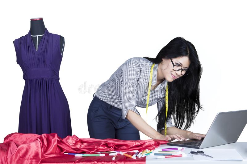 Young seamstress using a laptop on studio stock images