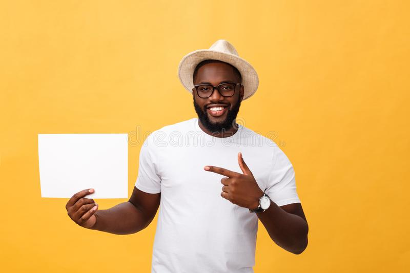 Picture of young smiling african-american man holding white blank board and pointing on it, on yellow background, copy royalty free stock photo