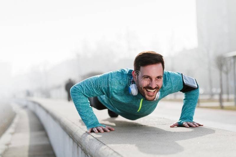 Picture of a young sportsman doing push ups outdoors. Fitness and exercising i stock photography