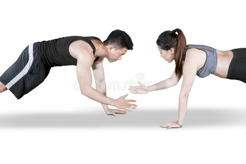 Sporty couple clap hands during push up on studio. Picture of young sporty couple clapping hands while doing push ups together in the studio stock photo
