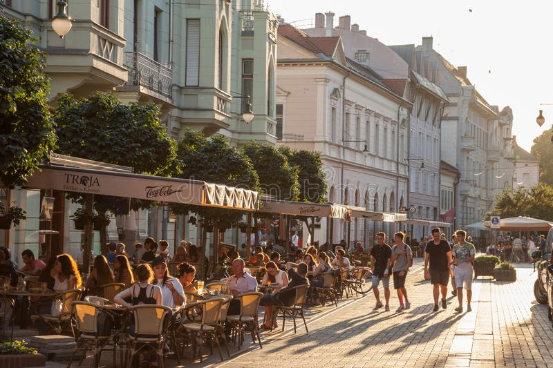Young people walking on a pedestrian street of Szeged, Southern Hungary, with other people sitting on tables in cafes & restaurant stock photography