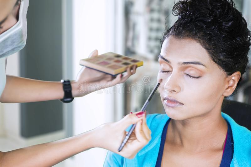 Woman applying eyeshadow powder to her client stock photo