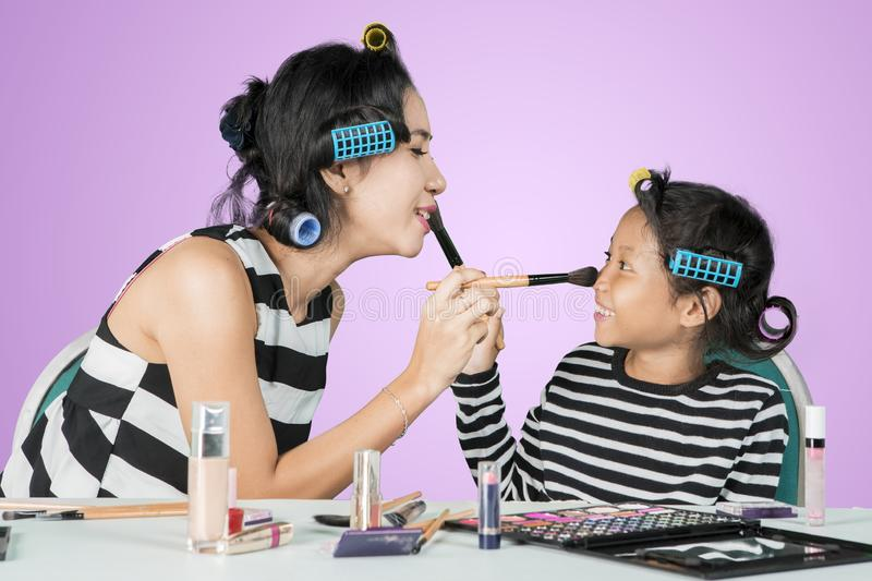 Woman and child doing makeup for each other royalty free stock image