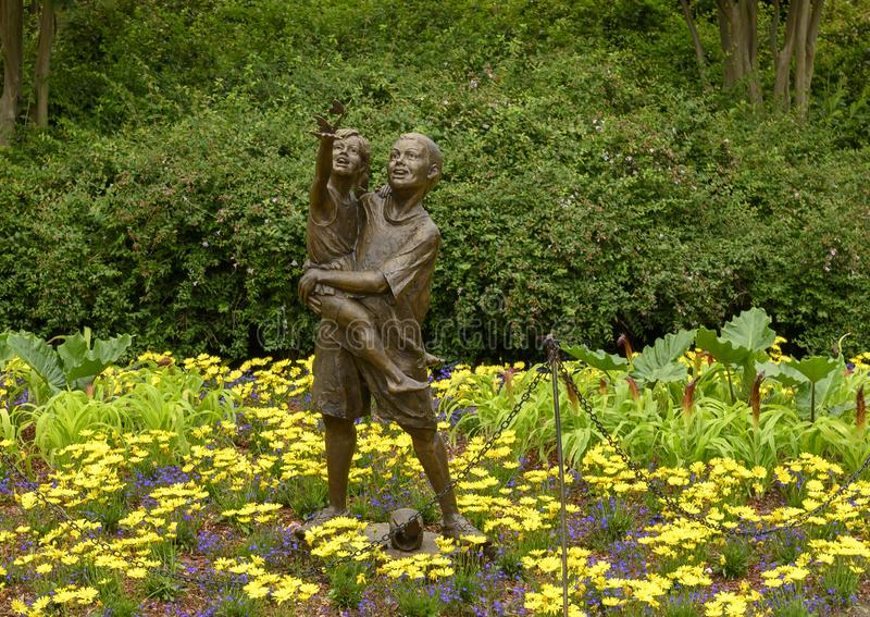 Bronze sculpture of a boy holding a girl releasing butterflies by Gary Price at the Dallas Arboretum and Botanical Garden stock images