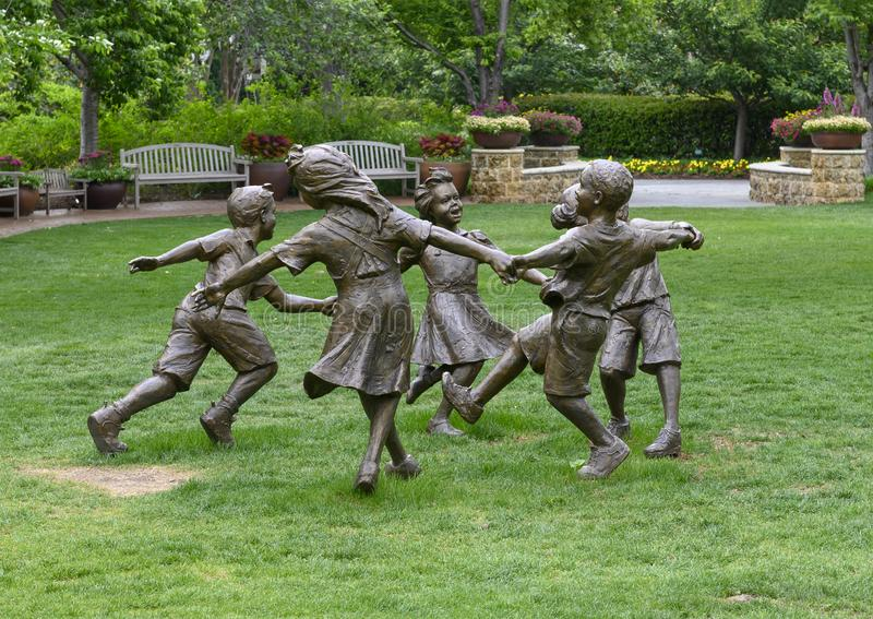 Bronze sculpture of children holding hands running in a circle by Gary Price at the Dallas Arboretum and Botanical Garden. Pictured is a Bronze sculpture of royalty free stock photos