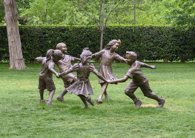 Bronze sculpture of children holding hands running in a circle by Gary Price at the Dallas Arboretum and Botanical Garden. Pictured is a Bronze sculpture of stock photography