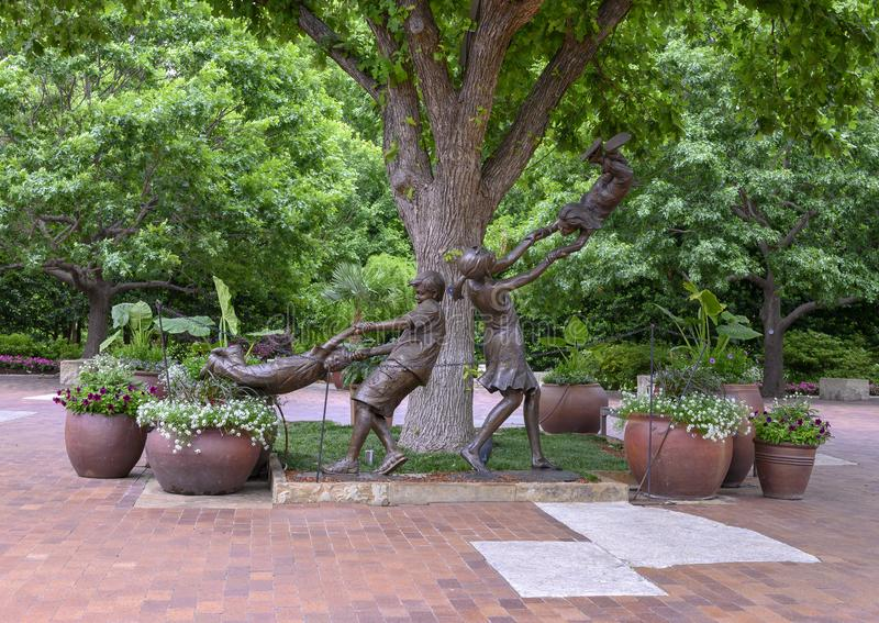 Bronze sculpture of children playing by Gary Price at the Dallas Arboretum and Botanical Garden royalty free stock photos