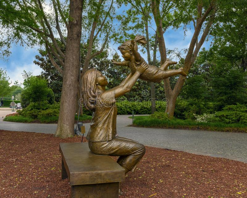 Bronze sculpture of woman holding up a happy child by Gary Price at the Dallas Arboretum and Botanical Garden. Pictured is a Bronze sculpture of a woman holding stock photos