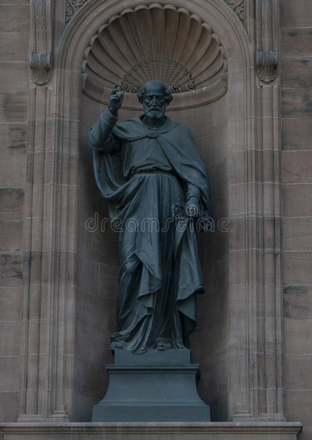 Bronze statue of Saint Peter in a niche on the front of the Cathedral Basilica of Saints Peter and Paul, Philadelphia. Pictured is a bronze statue of Saint Peter stock photo