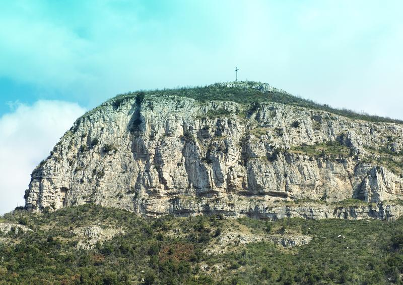 Distant view of a cross atop an mountain with sheer cliffs ouside Sorrento, Italy stock photo
