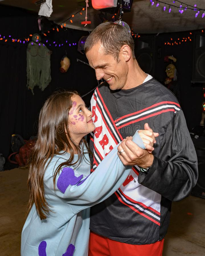 Father and daughter dancing at a Halloween party stock images