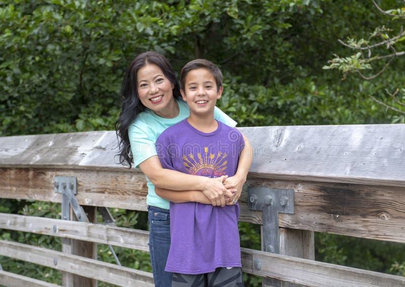 Korean mother and her Amerasian son posing on a wooden bridge in Washington Park Arboretum, Seattle, Washington stock images