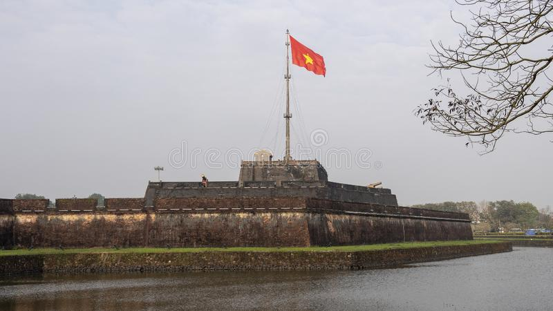The flag tower of Hue Citadel with the flag of Vietnam flying in the wind. Pictured is the flag tower of the Hue Citadel with the flag of Vietnam flying in the stock image