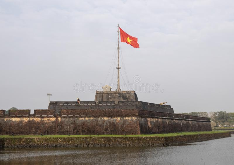 The flag tower of Hue Citadel with the flag of Vietnam flying in the wind. Pictured is the flag tower of the Hue Citadel with the flag of Vietnam flying in the royalty free stock photo