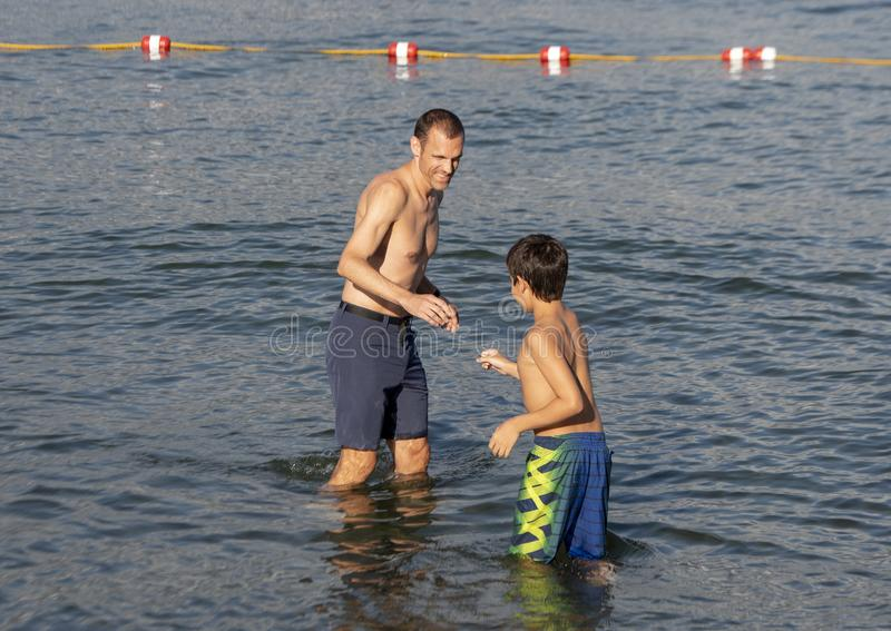 Father and son enjoying the lake in Greenlake Park, Seattle, Washington. Pictured is a forty-two year old physically fit father and his twelve year old Amerasian stock images