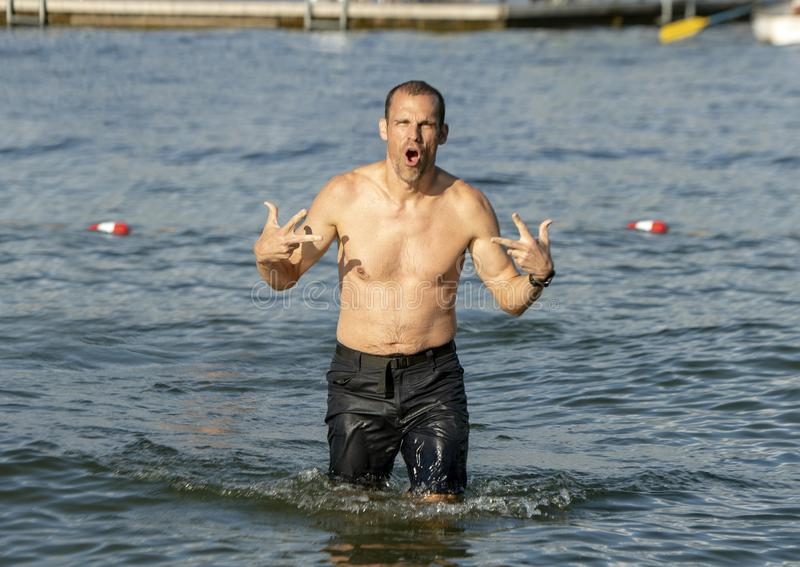 Forty-two year-old Caucasian man in fun pose in the lake at Greenlake Park, Seattle. Pictured is a fun pose by a forty-two year old fit Caucasian man as he walks stock photography