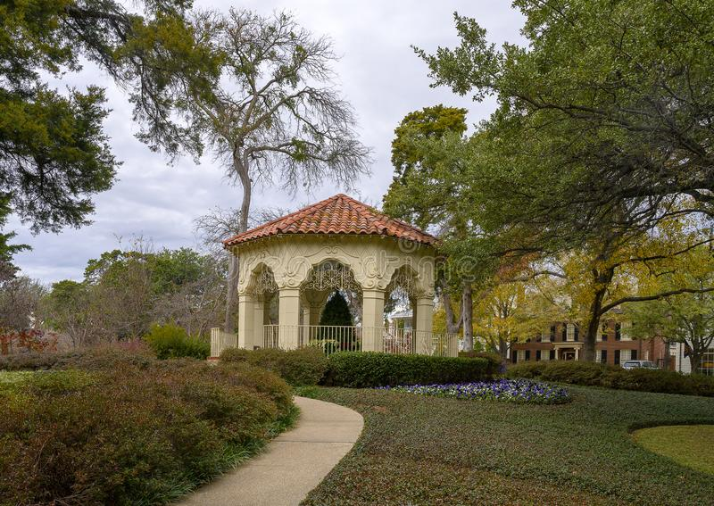 Gazebo, sidewalk, flower bed, bushes and trees in Flippen Park in Highland Park in Dallas, Texas stock photography