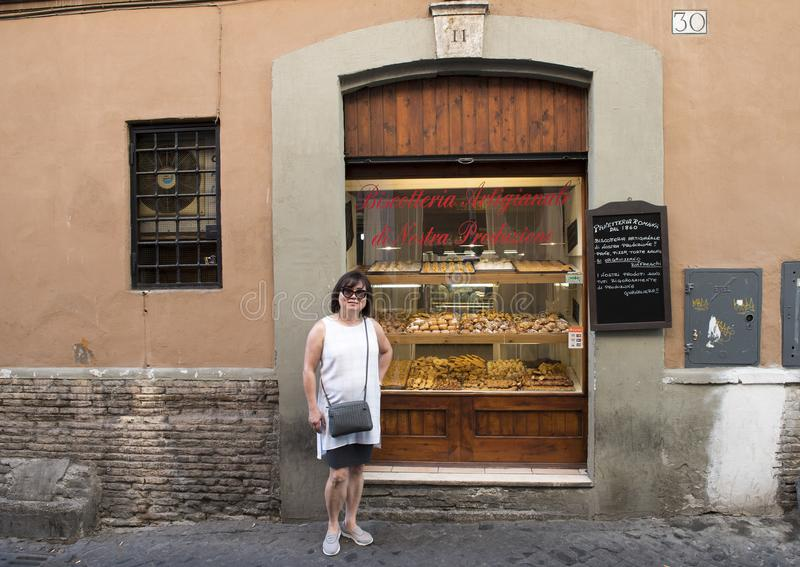 Korean woman on holiday in Rome debating a pastry purchase stock image