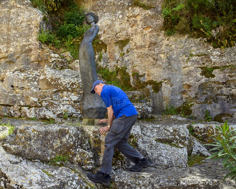 Older male caucasian tourist climbing down rocks after posing with `Marie`, a sculpture by Jean Philippe Richard in Eze, France royalty free stock photography