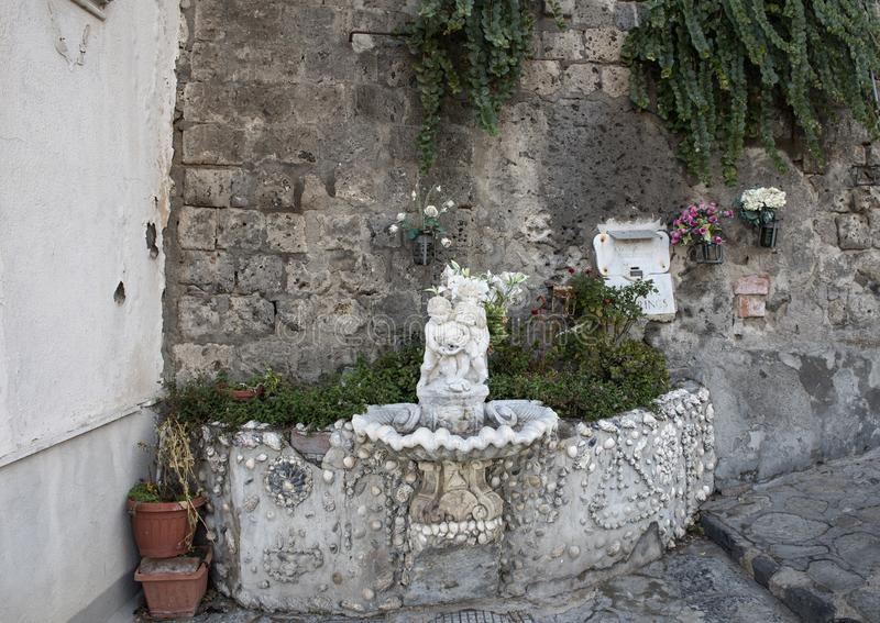 Ornate drinking fountain with small statue of a cherub holding a dolphin, Marina Grande, Sorrento. Pictured is an ornate drinking fountain with small statue royalty free stock image